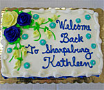 Photo of a cake with the words Welcome Back To Sharpsburg Kathleen written on top. Taken May 9, 2017. Photographer unknown.