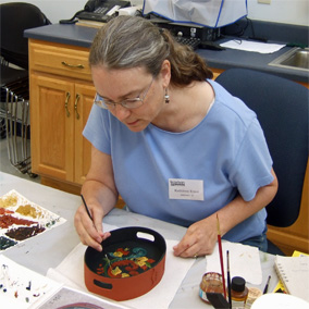 Bestselling author Kathleen Ernst taking a Rosemaling class at Vesterheim Norwegian-American Museum in Decorah, Iowa, where Heritage of Darkness, the fourth book in her award-winning Chloe Ellefson mystery series is set.