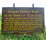 Photo of the wooden sign on Plum Creek marking where the Ingalls family ived in a dugout near Walnut Grove, Minnesota.