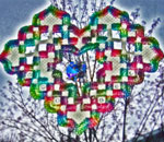 Color photo of woven Hardanger heart hanging in author Kathleen Ernst's kitchen window.