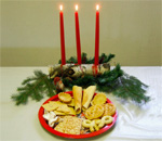 Photo of Norwegian Christmas cookies next to a fir bough and burning red candles. Photo by bestselling author Kathleen Ernst.