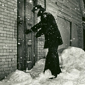 Photo of a Milwaukee Police Officer checking a door during a snowstorm.