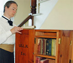 Author Kathleen Ernst in circa 1910 clothing examining the library box at Pottawatomie Lighthouse on Rock Island, WI.
