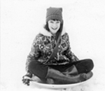 Author Kathleen Ernst as a child, sliding down a hill on a winter's day. Photo by Henry Ernst.