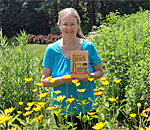 Bestselling author Kathleen Ernst hold an ARC (Advance Review Copy) of her sixth Chloe Ellefson mystery, Death on the Prairie, which comes out October 8, 2015 from publisher Midnight Ink Books.