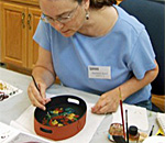 Photo of author Kathleen Ernst painting a tray in a rosemaling calss at Vesterheim Norwegian-American Museum in Decorah, IA.