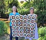 Photo of (L-R) authors Kathleen Ernst and Linda Halpin holding Linda's quilt of Laura Ingalls Wilder patterns at the sight of the Ingalls family dugout home on Plum Creek, near Walnut Grove, Minnesota.