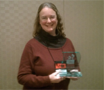Photo of author Kathleen Ernst holding the 2012 Lovey Award for Best Traditional Mystery book. Photo taken February 2, 2013 at the Love Is Murder mystery writer's conference in Chicago.