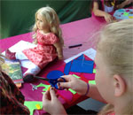 Photo of a little girl with her Caroline American Girl doll making a quilt at Sackets Harbor State Battlefield Park, New York, on July 11, 2015.