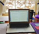 Photo by bestselling author Kathleen Ernst showing her laptop at a desk looking outside on a snowy winter day.