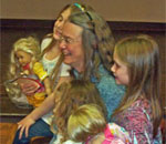Photo of award-winning author Kathleen Ernst posing with some of her American Girl fans April 18, 2013 at the public library in Lake Mills, WI.