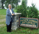 Photo of bestselling author Kathleen Ernst, creator of the American Girl historical character Caroline Abbott, at the Sackets Harbor Battlefield Historic Site in Caroline's hometown of Sackets Harbor, New York, in 2014.