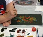 Photo of a rosemaling instructor's hands, painting.