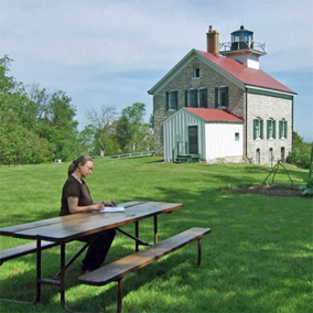 Bestselling author Kathleen Ernst writing The Light Keeper's Legacy, the third Chloe Ellefson historic sites mystery, at the Pottawatomie lighthouse on Rock Island, Wisconsin. Photo by Scott Meeker.