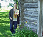 Photograph of bestselling author Kathleen Ernst, writer of the Chloe Ellefson Historic Sites mystery series, standing at the reproduction Ingalls cabin near Pepin, Wisconsin, holding a copy of The Little House in the Big Woods book written by children's author Laura Ingalls Wilder. Photo taken by Barbara Ernst.