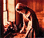Sepia tone 1982 photo of Kathleen Ernst in 19th century clothing working as an interpreter in the 1875 Schottler farm at the Old World Wisconsin outdoor history museum.