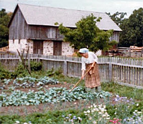 Then interpreter, now bestselling author Kathleen Ernst of the Chloe Ellefson historic sites mystery series, tending an heirloom garden at Old World Wisconsin in 1982. Photographer unknown.