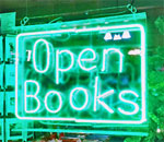 Photo of the Open Books neon sign in the window of the Mystery To Me bookstore in Madison, Wisconsin. Photo by Joanne Berg.