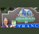 Bestselling author Kathleen Ernst holding her new non-fiction history book, A Settler's Year: Pioneer Life Throught The Seasons, in front of the entrnace sign for Old World Wisconsin, where the photos in the book were taken.