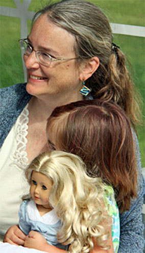 Bestselling author Kathleen Ernst and a young American Girl reader holding her Caroline doll, taken at Sackets Harbor, New York.