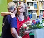 Author Kathleen Ernst receiving flowers from Mr Ernst at launch of Fiddling With Fate launch party at Mystery To Me books 10 September 2019