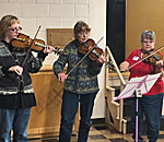 Three Hardanger fiddle players performing at the Sons of Norway Idun Lodge in Madison Wisconsin 02 October 2019.