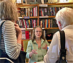 Photo of bestselling author Kathleen Ernst signing her Chloe Ellefson mysteries at Fair Isle bookstore on Washington Island by Mr Ernst..