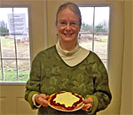 Bestselling author Kathleen Ernst, who wrote The Lacemaker's Secret, the 9th Chloe Ellefson mystery, holding the Belgian cherry pie she baked in a class taught by Gina Guth in Door County, Wisconsin.