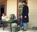 American Civil War reenactor Larry Hackney at the Four Mile Inn, at Old World Wisconsin, during a reenactment of the military draft.  Note the lottery wheel on the table. Photographer unknown, taken circa mid-1980s.