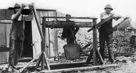 A human-powered windlass used for lowering and lifting miners and raising ore and rubble out of a primitive sub-surface lead mine in southwestern Wisconsin. Photographer unknown. Image taken circa late 1800s. Wisconsin Historical Society Image 8990 cropped.