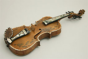 Color photo of a Hardanger fiddle decorated with dancing devils. Vesterheim Norwegian-American Museum collection. Used with permission.