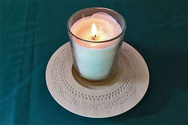 <strong>Chip carved wooden candle plate.</strong> The beautiful design on this piece is an example of what someone in Emil's Norwegian chip carving course might create for their class project. (Candle plate by Ellen Macdonald. Photo by author.)