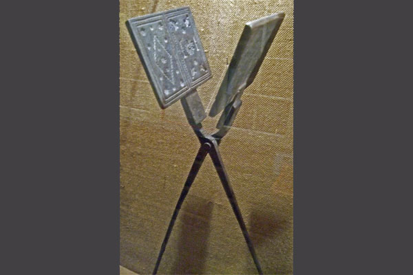<strong>Long handle metal waffle iron.</strong> At the Valdres House Marit demonstrates baking with a heavy decorative waffle iron like this. (Vesterheim Norwegian-American Museum. Photo by author.)