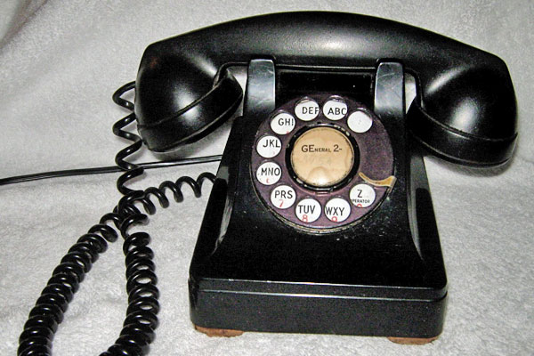 Chloe discovers her office phone, an old rotary dial model like this, when Byron calls to say Mrs. Lundquist is on her way to meet Chloe at the trailer. (Photographer unknown.)