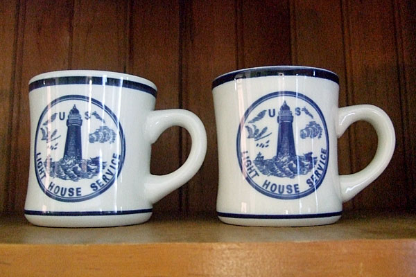<strong>Light House Service China.</strong> These coffee mugs are reproductions of original U.S. Light House Service china that was at the Pottwatomie Lighthouse when Emily Betts arrived. (Photo by the author.)