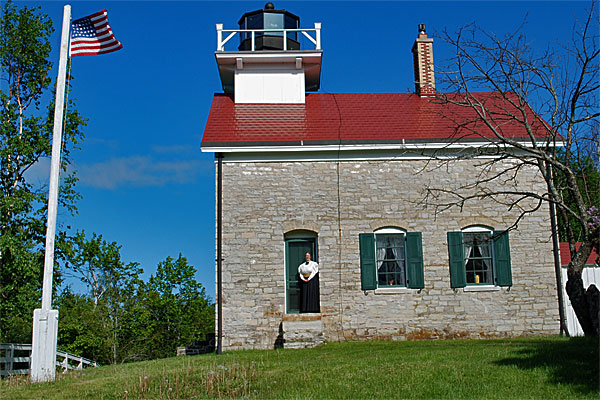 <strong>Pottawatomie Lighthouse Today.</strong> This image shows the lighthouse as it existed in 2012, some 130-years after the previous photo, and 154-years after it was built. The author is standing at the front door. (Photo by Kay Klubertanz.)
