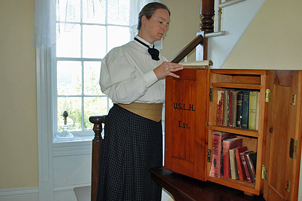 <strong>Traveling Library Box.</strong> The author, serving as a docent at the Pottwatomie Lighthouse, examines a book from the reproduction library box. Chloe finds an important clue in an original US Lighthouse Service library box. (Photo by Kay Klubertanz.)