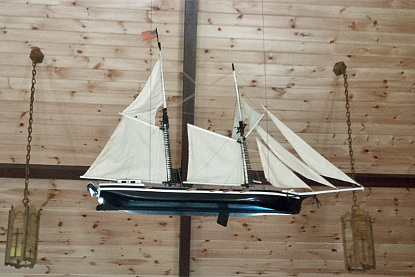 <strong>Scandinavian Tradition.</strong> Chloe contemplates this hand-carved model of the sailing ship <em>The Madonna</em> hanging from the sanctuary ceiling in the Trinity Lutheran Church on Washington Island. (Photo by Scott Meeker.)